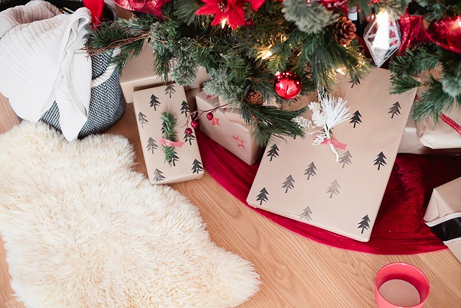 Christmas gifts wrapped with tree stamps on under Christmas tree