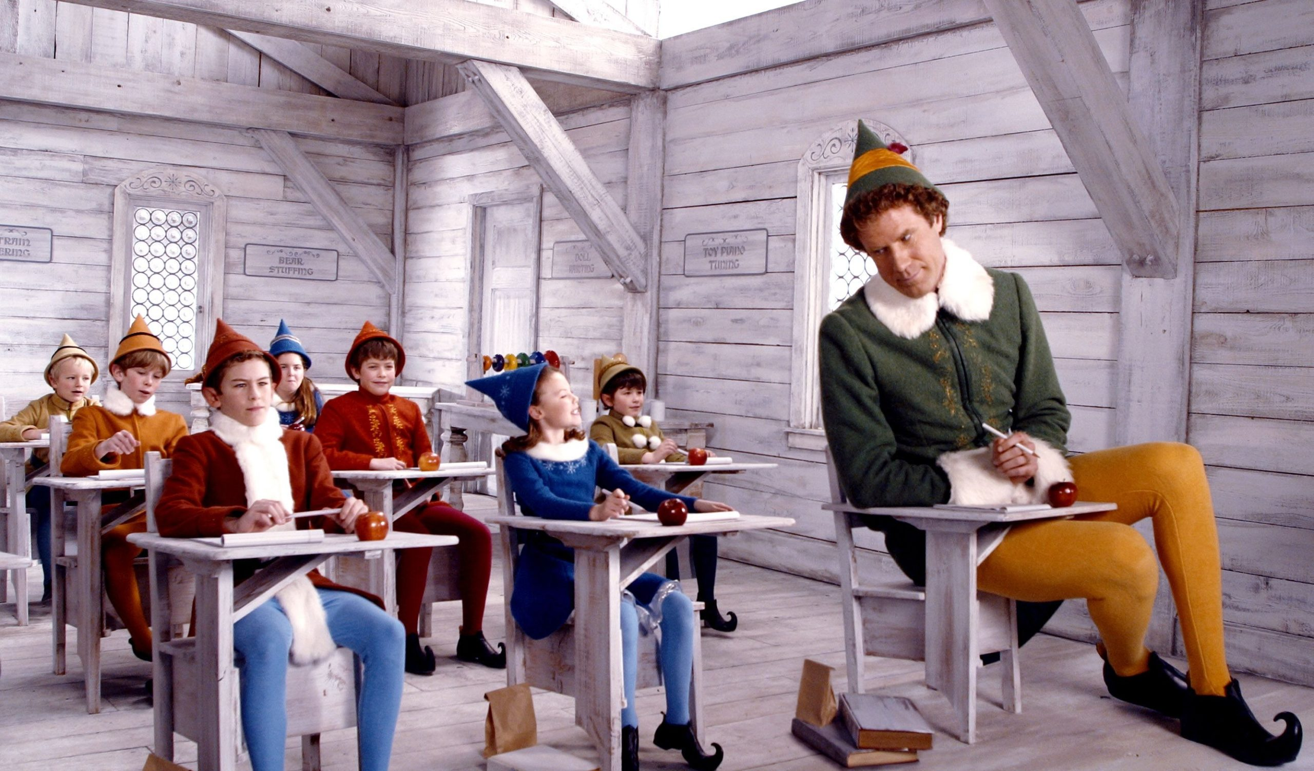 Will Ferrell Buddy the Elf sitting on school desks with other elves